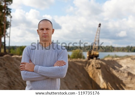 Portrait of worker  at sand pit - stock photo