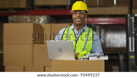 Portrait of worker in warehouse with laptop computer - stock photo