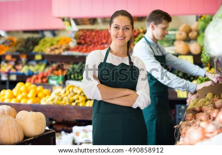 portrait of workers selling fresh fruits and vegetables on market
