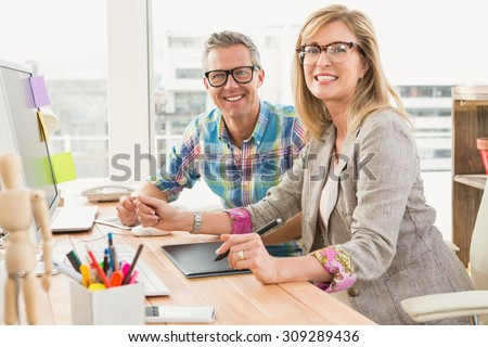 Portrait of working creative design team smiling to camera in the office - stock photo