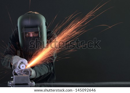 Portrait of workman in black mask, isolated on black - stock photo