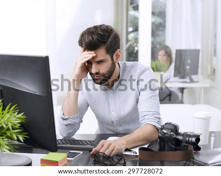 Portrait of worried young businessman sitting in front of computer at office.  - stock photo