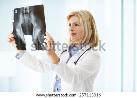 Portrait of x-ray specialist analyzing x-ray image while standing at hospital.  - stock photo
