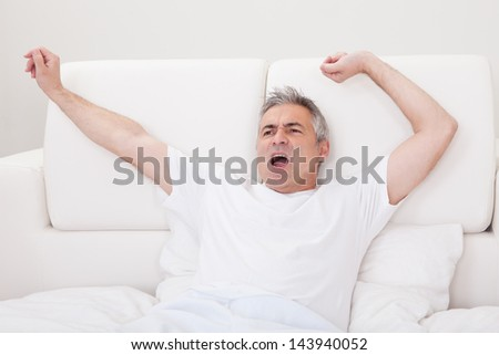 Portrait Of Yawning Mature Man Stretching His Arms In Bed
