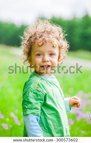 Portrait of 1 year old baby boy having fun on a mountain meadow. - stock photo