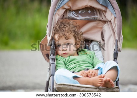 Portrait of 1 year old baby boy in a stroller. - stock photo