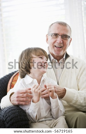 Portrait of 9 year old boy laughing with grandfather - stock photo