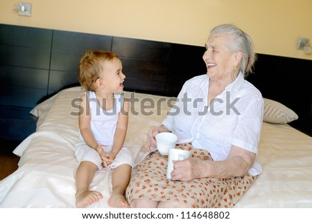 Portrait of 1,5 years old baby and and her 91,5 years old great grandmother - stock photo