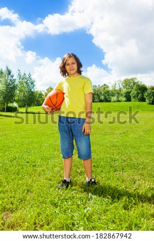 Portrait of 12 years old boy hold basketball ball on the field on bright sunny day - stock photo
