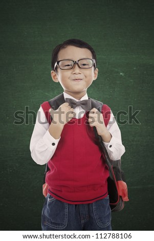 Portrait of 5 years old boy standing in front of blackboard and ready to school - stock photo