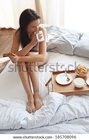 Portrait of 30 years old woman resting in bed with breakfast on a wooden tray at home in morning, still life photo - stock photo