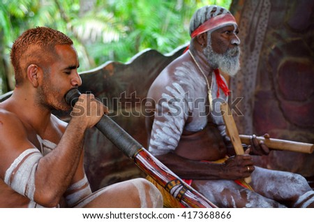 Portrait of Yirrganydji Aboriginal men play Aboriginal music on didgeridoo and wooden instrument during Aboriginal culture show in Queensland, Australia.