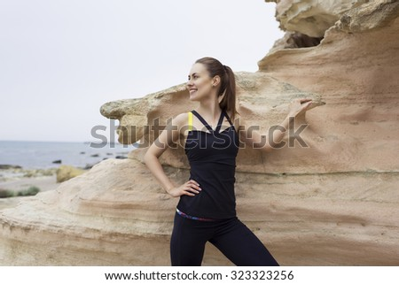 Portrait of young active woman smiles while taking break after workout outdoors in beautiful nature,female runner resting after jogging in sea and mountain rocks landscape, sportive women taking break - stock photo