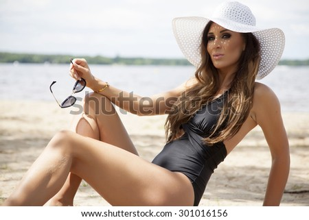 Portrait of young adult beautiful sensuality sexy and attractive brunette pretty woman in fashionable black swimwear bikini dress and white hat and sunglasses on the sunny beach in summertime - stock photo