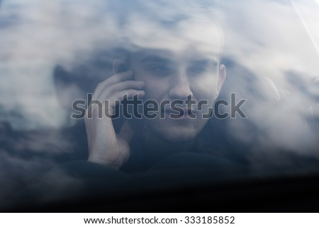 portrait of young adult behind steering wheel inside a car making a phone call with his smartphone - stock photo