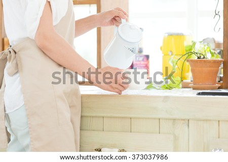 Portrait of young adult brunette asian woman making tea or green tea on kitchen room - stock photo