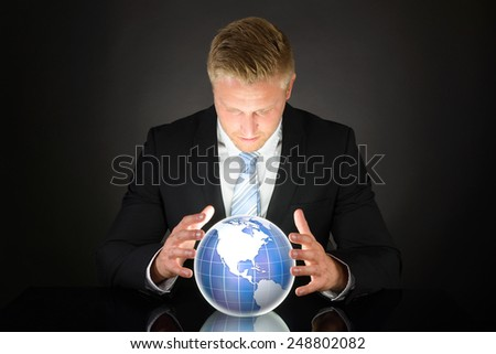 Portrait Of Young Adult Businessman Looking At Globe