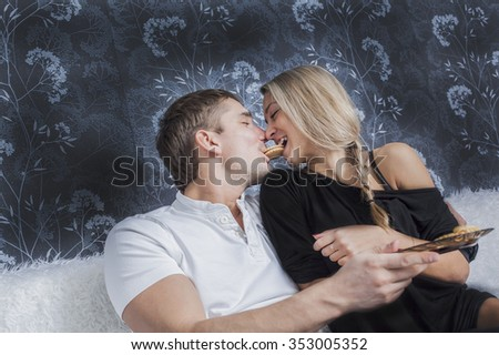 Portrait of young adult caucasian couple sit on white wool couch together eating cookie Man holding sweet between lips Woman bite food Empty texture Copy space for inscription White and black clothes - stock photo