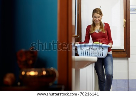 portrait of young adult caucasian woman leaning on washing machine and looking at camera with clothes basket. Horizontal shape, front view, copy space