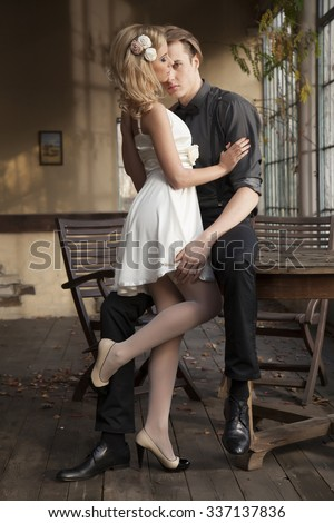Portrait of young adult couple in love posing in retro classic elegance clothes to date - stock photo