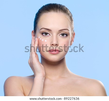 Portrait of young adult girl applying cream on her  skin around eyes - blue background