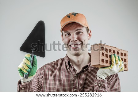 portrait of young adult happy mason tradesman in a red plaid shirt holding red brick with holes and black trowel on gray background Handsome man look at camera with smile wear green rubber gloves - stock photo