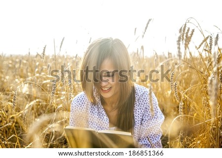 Portrait of young adult latin hispanic girl sitting on reap golden wheat summer field, reading black book Cute asian woman on autumn yellow meadow and sky background - stock photo