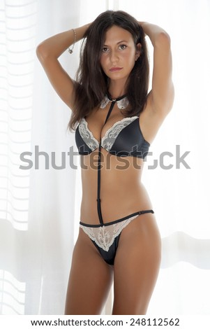Portrait of young adult sensuality slim sexy and attractive pretty brunette beauty woman in black lingerie against the window on luxury style apartment - stock photo