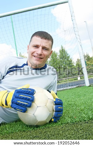Portrait of young adult Soccer football goalkeeper lie on fresh green grass on gate net and blue cloudy sky background Goalkeeper looking at camera - stock photo