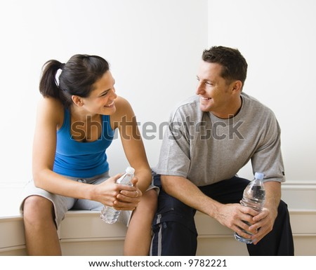Portrait of young adult woman and man sitting wearing active wear. - stock photo