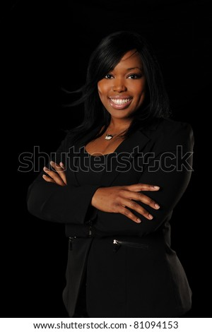 Portrait of young African American businesswoman smiling with arms crossed isolated over black background - stock photo