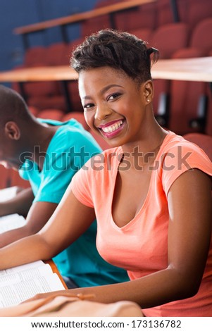 portrait of young african american female college student in lecture room - stock photo