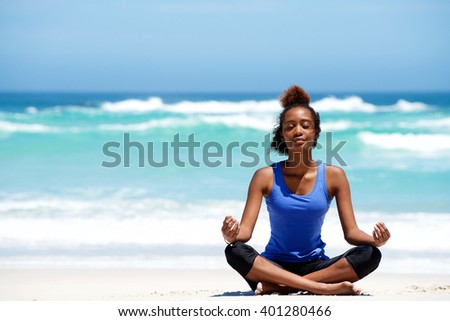 Portrait of young african american woman meditating in yoga pose outdoors at the beach - stock photo