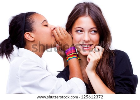 portrait of young african american woman telling a secret to a caucasian woman over a white background - stock photo