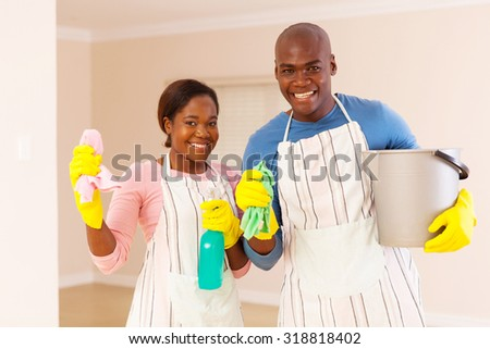 portrait of young african couple cleaning their new house