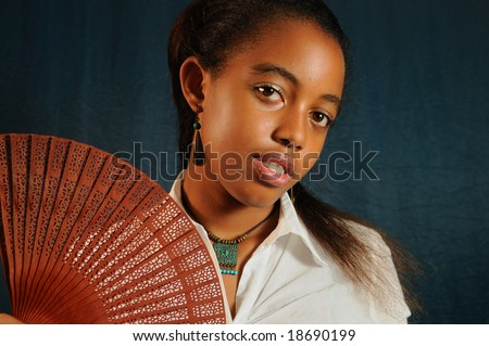 Portrait of young african fashion teenage female with fan - stock photo