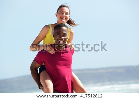 Portrait of young african guy piggybacking his girlfriend outdoors on the beach - stock photo