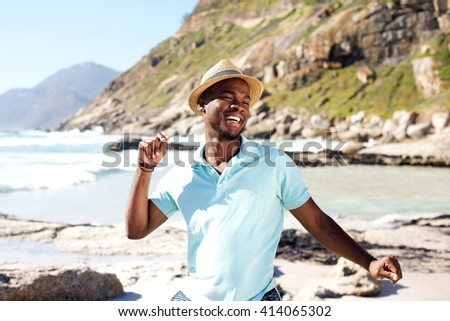 Portrait of young african man dancing at the beach on summer day - stock photo