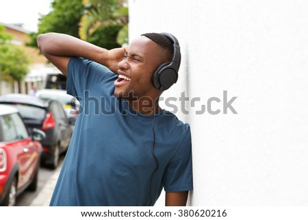 Portrait of young african man enjoying listening to music on headphones while leaning to a white wall outdoors - stock photo