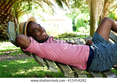 Portrait of young african man relaxing outdoors on a hammock on a summer day - stock photo