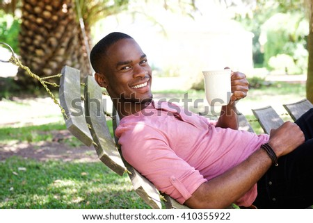 Portrait of young african man relaxing outdoors on hammock with a coffee - stock photo