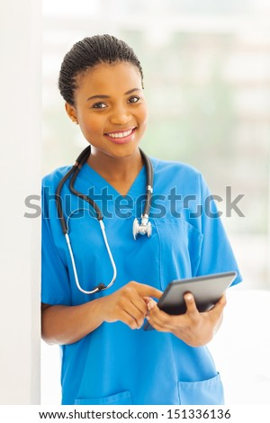 portrait of young african nurse using tablet pc - stock photo