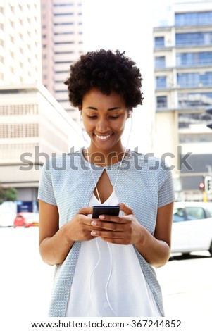 Portrait of young african woman wearing earphones listening to music on the mobile phone - stock photo