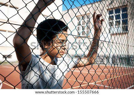 Portrait of young afro-american boy in a basketball court - stock photo
