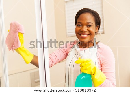 portrait of young afro american woman cleaning shower door
