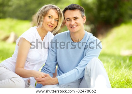Portrait of young amorous couple looking at camera in park - stock photo