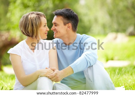 Portrait of young amorous couple looking at each other in park