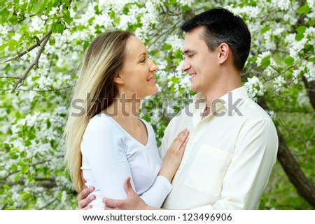 Portrait of young amorous couple looking at one another in park - stock photo