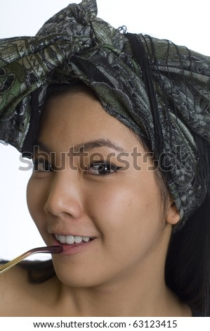 Portrait of young and beautiful Asian woman wearing a head scarf - stock photo