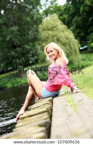 Portrait of young and beautiful blonde beside a city canal